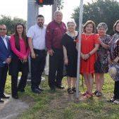 City Council, Mayor Armando O'Caña, and Oton Guerrero's children stand in front of the memorial street sign.