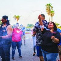 Sandra Vicencio and RGV Big Dawg members wave sparklers for the patients watching from their rooms.